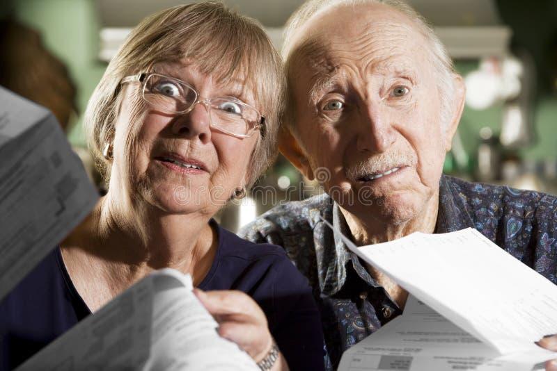 Ältere Paare mit Rechnungen stockbilder