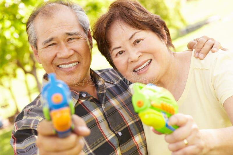 Ältere Paare mit Wasserpistolen lizenzfreie stockfotografie