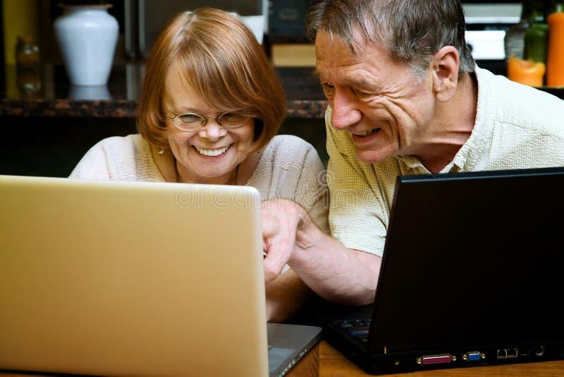 Ältere Paare unter Verwendung der Laptop-Computer zu Hause lizenzfreie stockfotografie