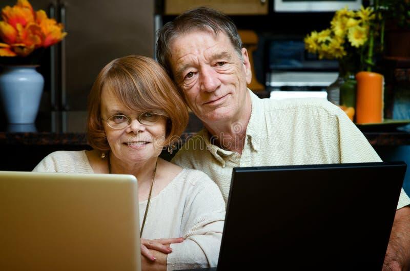 Ältere Paare unter Verwendung der Laptop-Computer zu Hause stockfotografie