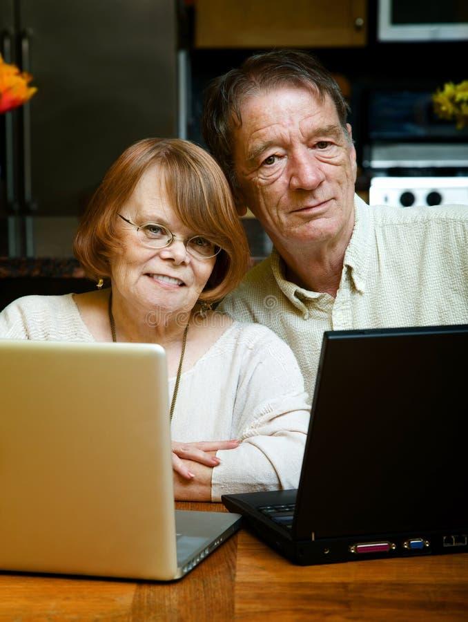 Ältere Paare unter Verwendung der Laptop-Computer zu Hause lizenzfreie stockbilder