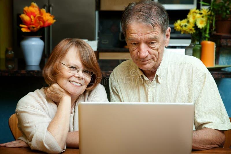 Ältere Paare unter Verwendung der Laptop-Computers zu Hause lizenzfreie stockfotos