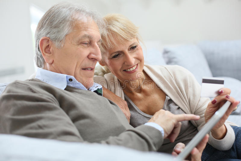 Ältere Paare unter Verwendung der Tablette stockbilder