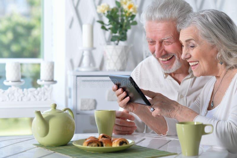 Ältere Paare unter Verwendung der Tablette beim Trinken des Tees lizenzfreie stockfotografie