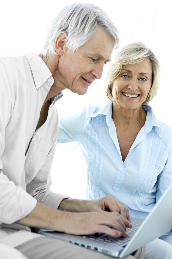 Ältere Paare unter Verwendung des Laptops lizenzfreie stockfotos