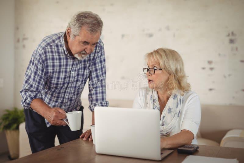 Ältere Paare unter Verwendung des Laptops stockfoto