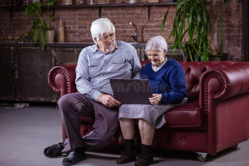 Ältere Paare unter Verwendung des Laptops beim Sitzen auf Couch lizenzfreies stockfoto