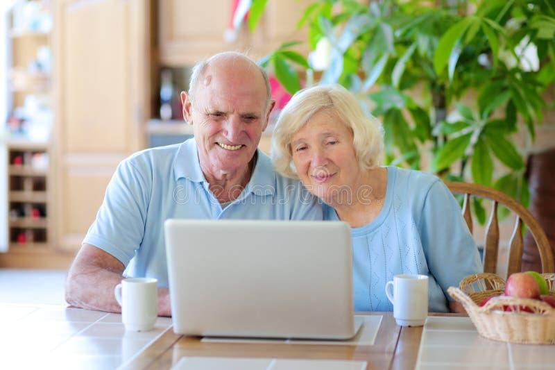Ältere Paare unter Verwendung des Laptops zu Hause stockbilder