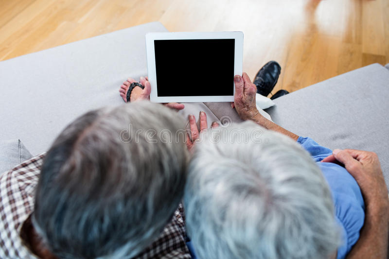 Ältere Paare unter Verwendung einer digitalen Tablette auf Sofa lizenzfreie stockbilder