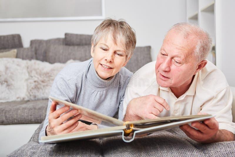 Ältere Paare von Bürgern mit Fotoalbum stockbilder