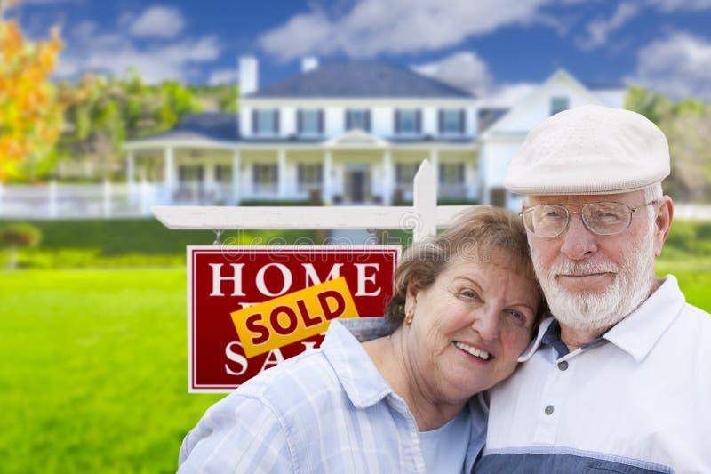 Ältere Paare vor Verkaufs-Real Estate-Zeichen und -haus stockbild