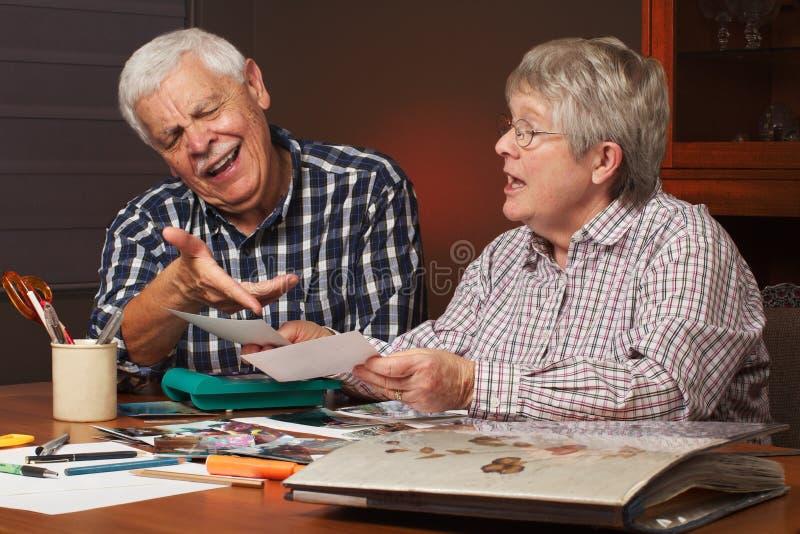 Ältere Paare wählen Fotos für Album lizenzfreie stockbilder
