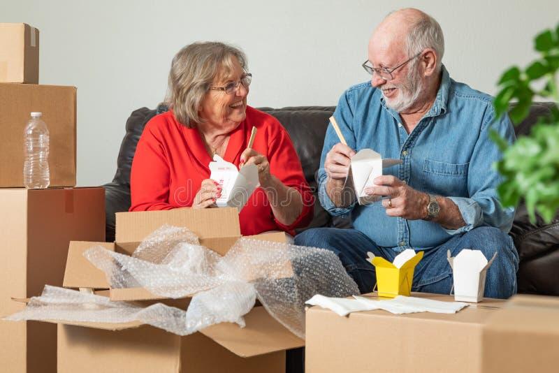 Ältere Paare, welche die chinesische Nahrung umgeben durch die Bewegung von Kästen teilen lizenzfreie stockfotos