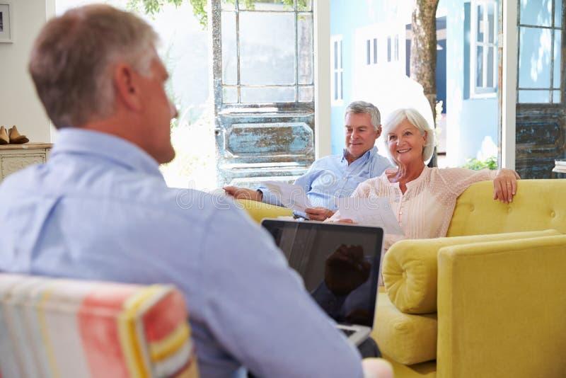 Ältere Paare zu Hause, die Finanzberater treffen lizenzfreies stockfoto