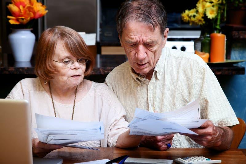 Ältere Paare zu Hause mit vielen Rechnungen stockfotografie