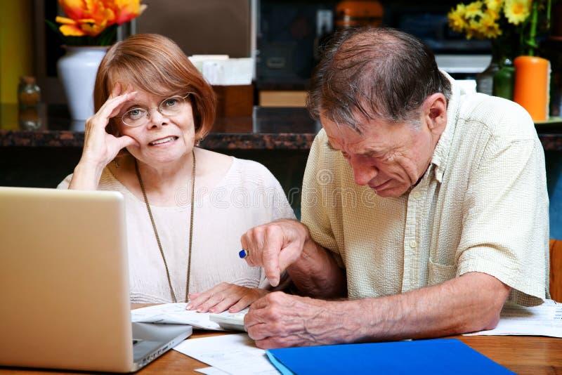 Ältere Paare zu Hause mit vielen Rechnungen stockbild