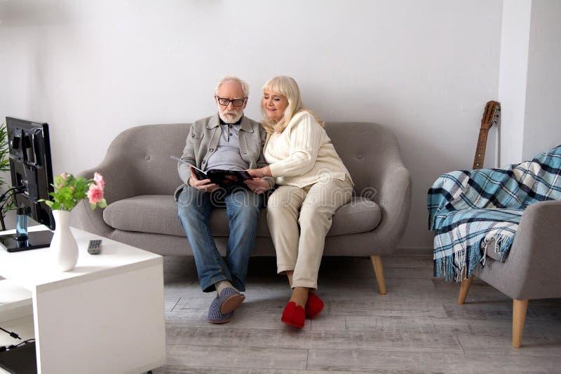 Ältere Paarlesung auf Couch lizenzfreies stockbild