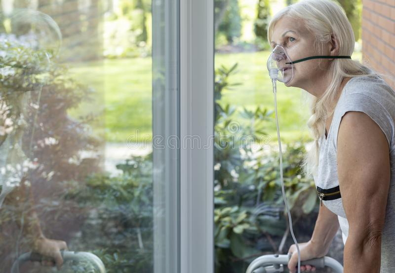 Ältere Person mit einer Sauerstoffatemmaske, die ein Fenster betrachtet lizenzfreies stockbild