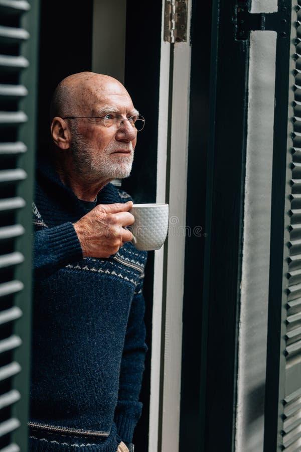 Ältere Personenstellung nahe dem trinkenden Kaffee der Tür Trinkender Kaffee der alten Person beim Schauen aus der Tür heraus stockbild