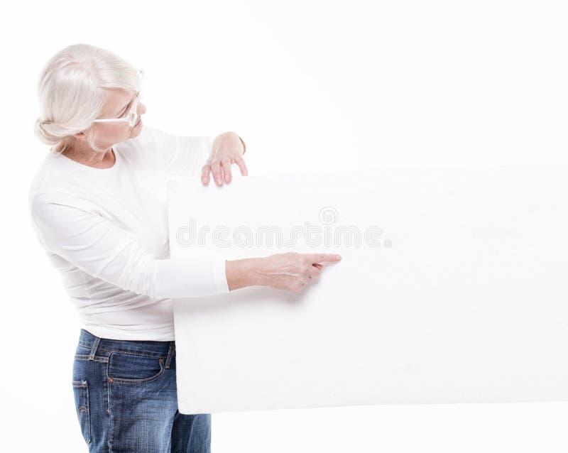 Ältere Schönheit mit leerem weißem Brett lizenzfreie stockfotografie