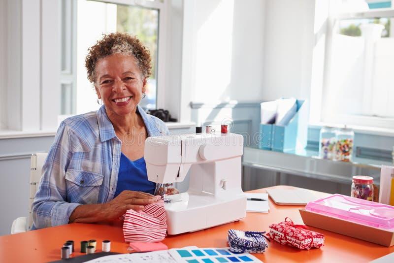 Ältere schwarze Frau, die eine Nähmaschine schaut zur Kamera verwendet stockbilder