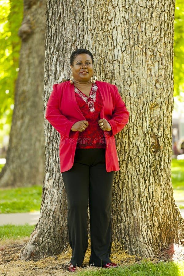 Ältere schwarze Frau, die rote Jacke im Freien steht lizenzfreie stockfotografie