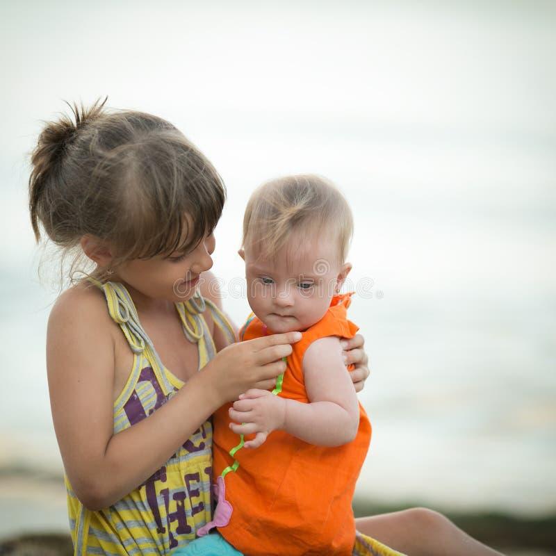 Ältere Schwester hält ein schönes Mädchen mit Down-Syndrom stockbilder