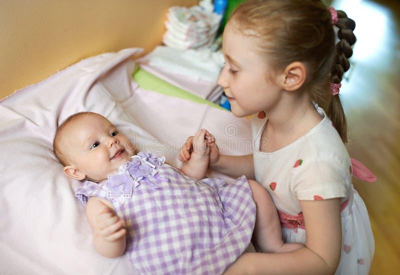 Ältere Schwester kümmert sich um dem kleinen Mädchen lizenzfreie stockfotos
