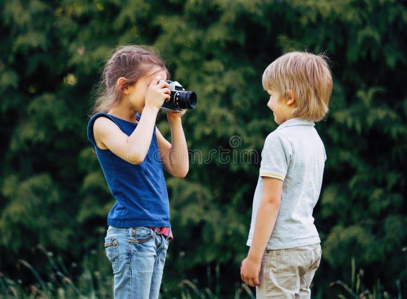 Ältere Schwester macht ein Foto seines Bruders auf dem Hintergrund des Parks stockbild