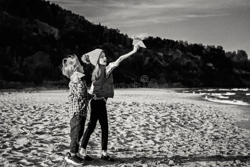 Ältere Schwester und jüngerer Bruder, Papierflächen auf Ozeanseestrand spielend stockbilder
