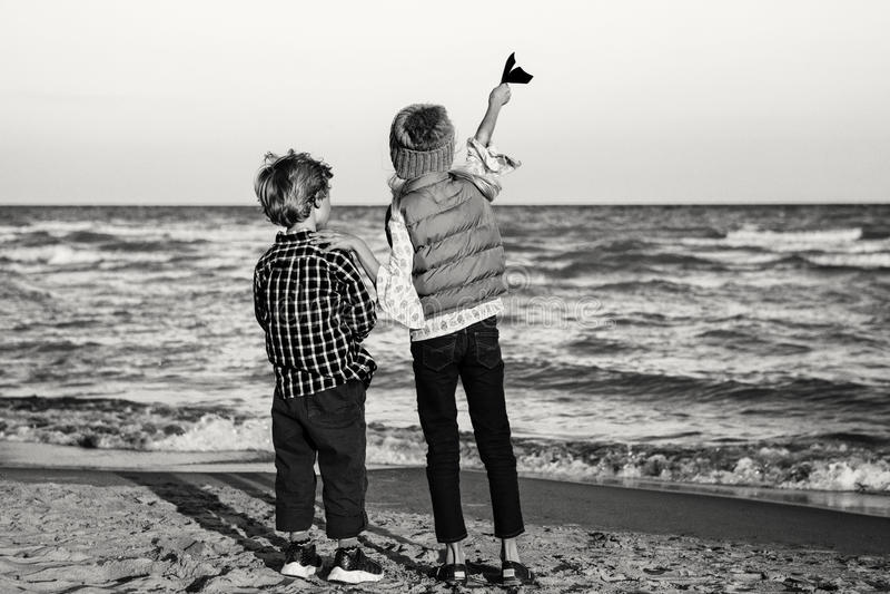Ältere Schwester und jüngerer Bruder, Papierflächen auf Ozeanseestrand spielend lizenzfreies stockfoto
