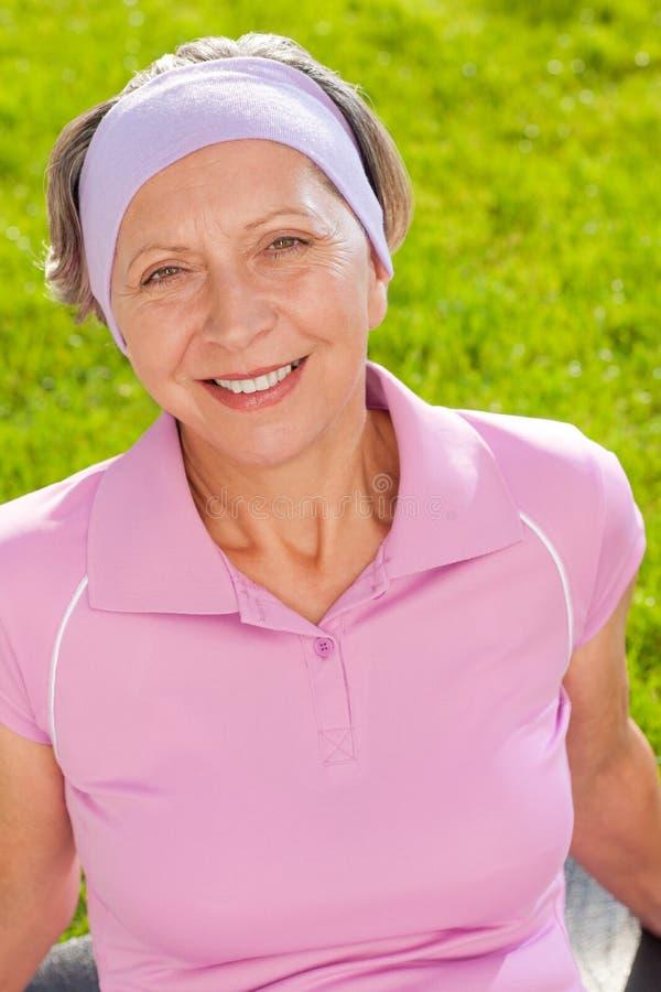 Ältere sportive Frau, die außerhalb des Portraits lächelt stockfoto