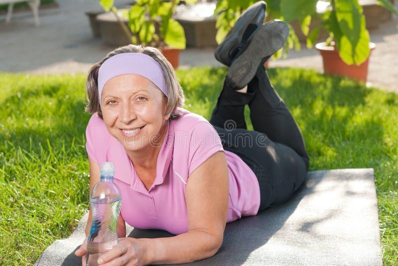Ältere sportive Frau, die auf der Matte sonnig liegt lizenzfreie stockfotografie