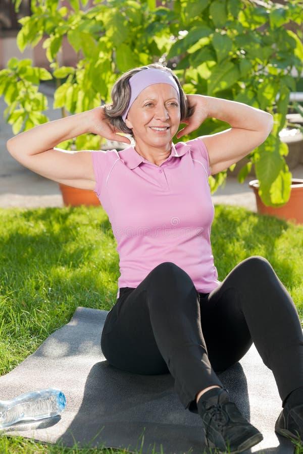Ältere sportive Frau, die sonnigen Tag des Sit-ups tut stockfoto