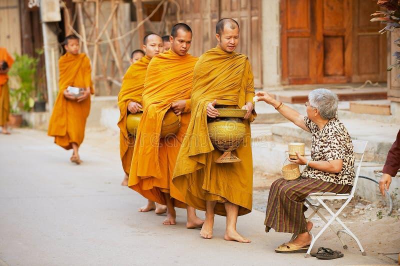 Ältere thailändische Frau bietet klebrigen Reis buddhistischen Mönchen morgens an der Straße in Chiang Khan, Thailand an stockfotos