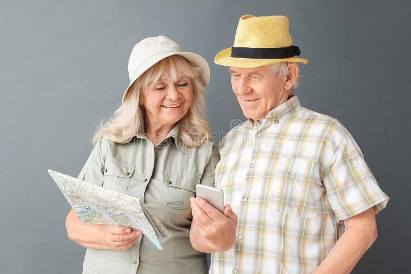 Ältere Touristen im Strandhutstudio, das auf Grau mit Kartenfrauenvertretungs-Ehemannbildern auf Smartphone steht lizenzfreies stockbild