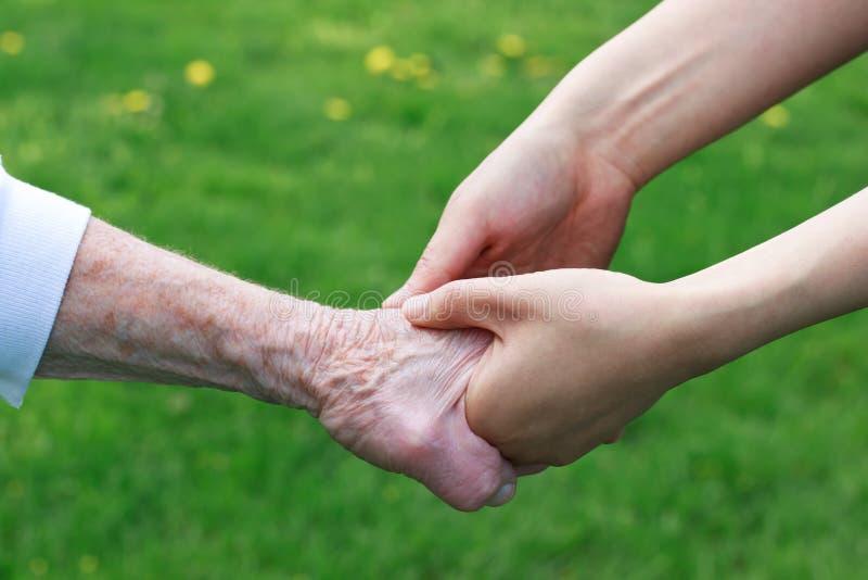 Ältere und junge Frauen, die Hände anhalten stockbild