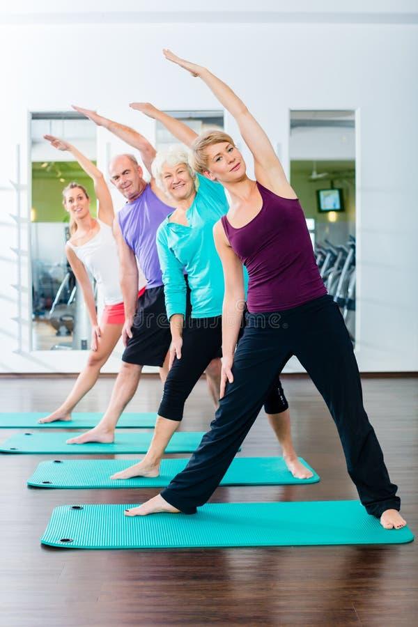 Ältere und junge Leute, die Gymnastik in der Turnhalle tun stockbild