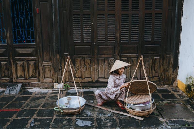 ältere vietnamesische Frau, die Lebensmittel auf Straße in Hoi An, Vietnam verkauft stockbild