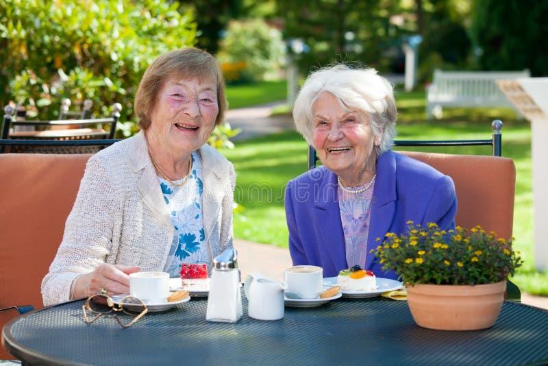 Ältere weibliche beste Freunde, die am Tisch sich entspannen stockfoto