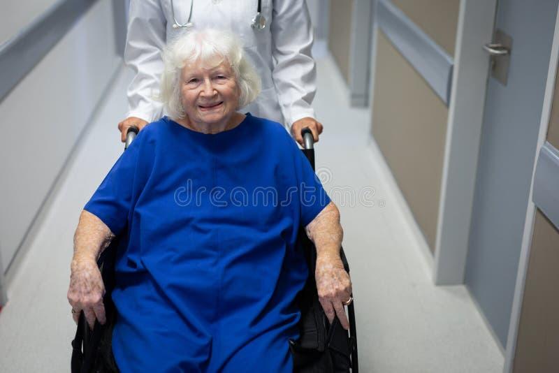 Ältere weibliche Patienten- und Doktorstellung in der Krankenhausklinik stockfoto