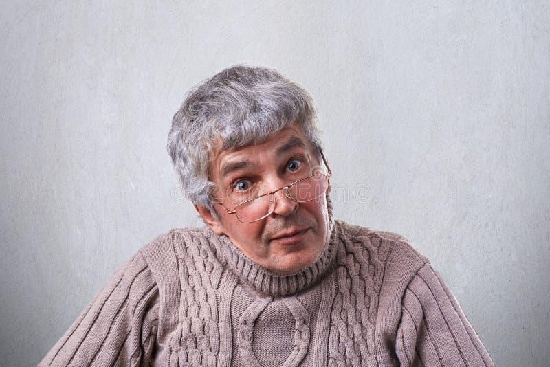 Älterer, älterer Mann in den Gläsern, die mit den weit geöffneten Augen haben klugen Ausdruck schauen Ein kluger Großvater in den stockfotografie