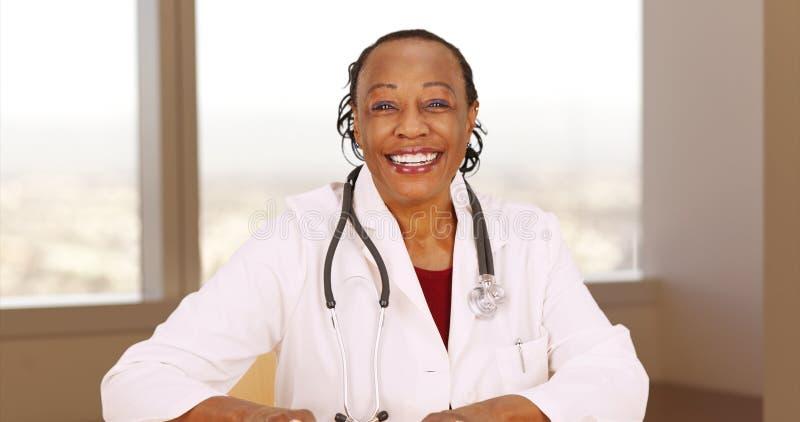 Älterer afrikanischer Doktor, der an der Kamera lächelt stockbilder