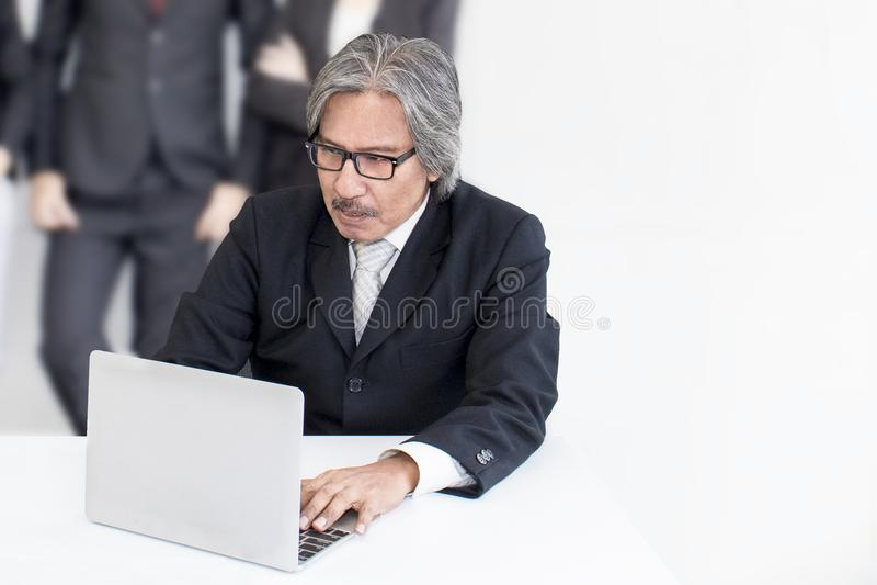 Älterer alter Mann des Geschäfts ernst im Büro Er schauend lächelnd lizenzfreie stockfotografie