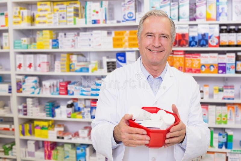 Älterer Apotheker, der Schüssel Medizin hält lizenzfreie stockbilder
