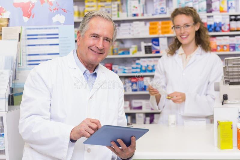 Älterer Apotheker, der Tabletten-PC verwendet stockfoto