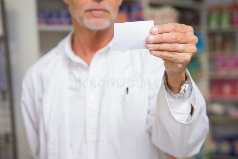 Älterer Apotheker, der Telefonkarte hält lizenzfreies stockbild