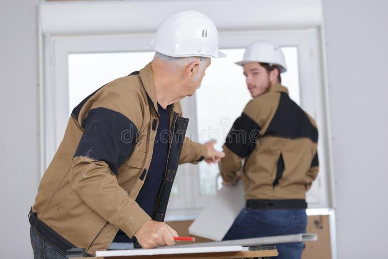 Älterer Architekt und junge Erbauerdiskussion stockfoto