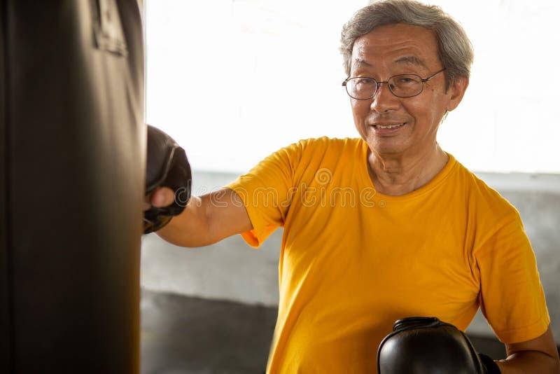 Älterer asiatischer Sportmann im Boxhandschuhsandsack in der Eignungsturnhalle männliches Trainieren des Ältesten, Training, Trai stockbild