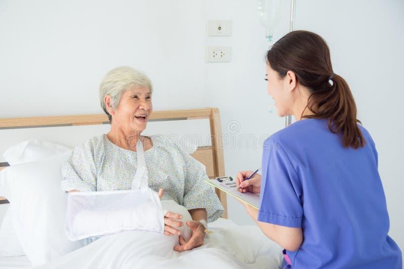Älterer asiatischer weiblicher Patient, der mit Krankenschwester lächelt lizenzfreie stockfotografie